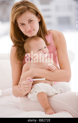 Woman holding a pregnancy test stick with her daughter sitting on her lap - Stock Photo