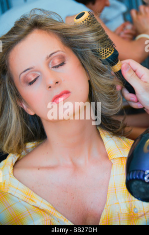 Woman getting her hair done at hair salon. - Stock Photo