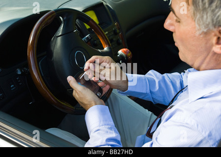 Man using a personal data assistant in a car - Stock Photo