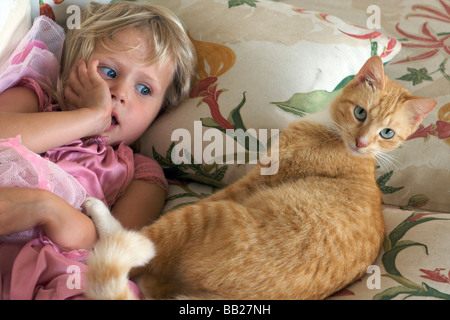 Four year old girl on the couch with her cat - Stock Photo