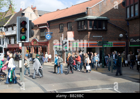 Pedestrians using a pedestrian crossing to cross the road while the traffic lights are on green in York England - Stock Photo