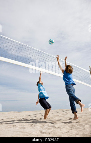 Woman with her grandson playing beach volleyball - Stock Photo