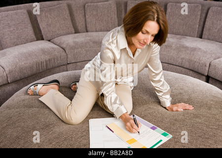 Woman filling out an application form - Stock Photo