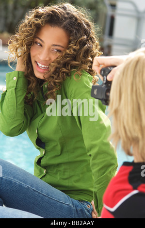 Teenage boy taking a picture of a girl with a digital camera - Stock Photo