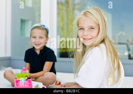 Portrait of two girls playing with toys - Stock Photo