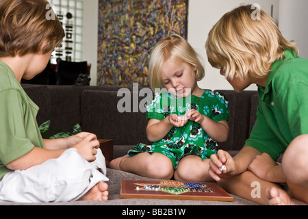 Girl playing Chinese checkers with her friends - Stock Photo