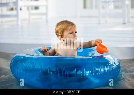 Baby boy sitting in an inflatable ring - Stock Photo