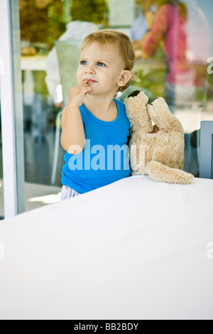 Baby boy holding a teddy bear and looking up - Stock Photo