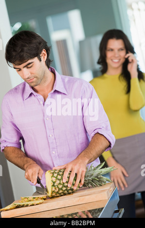 Man cutting a pineapple and a woman talking on a mobile phone behind him - Stock Photo