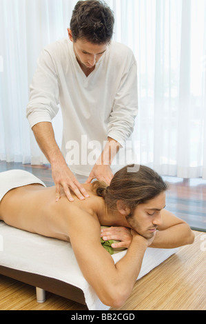 Man receiving a back massage from a massage therapist - Stock Photo