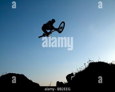 Boy riding a bike and making a big jump - Stock Photo