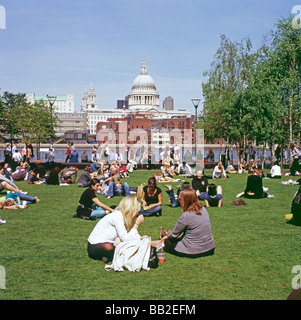 People relaxing in sunshine on the lawn outside the Tate Modern Art Gallery view of St Paul's Cathedral on London - Stock Photo