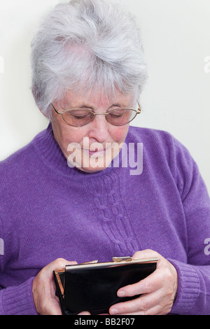 Close up of a penniless British pensioner looking into an empty purse in her hands with concerned expression in - Stock Photo