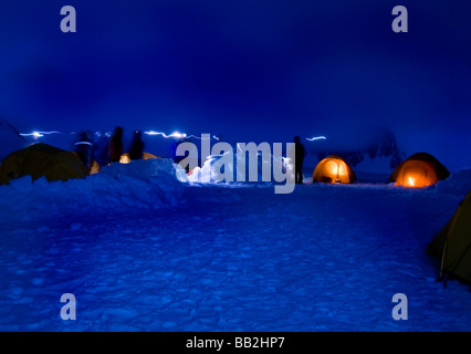 Expedition team members camping near Dorian Bay in Antarctica silhouetted as darkness falls - Stock Photo