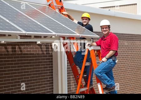 Happy electricians employed to install energy efficient solar panels in the new green economy  - Stock Photo