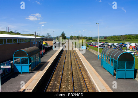 Corbridge railway station with glimpse of car boot fair in field - Stock Photo