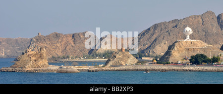 Muscat Oman waterfront with rocky coastline &  incense burner watch tower on hillside including small hilltop forts - Stock Photo