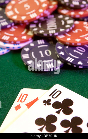 casino chips and playing cards on a casino playing table - Stock Photo