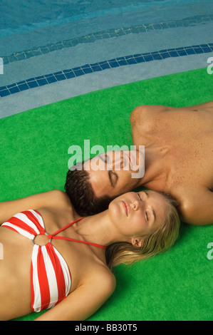 Couple sunbathing at the poolside - Stock Photo