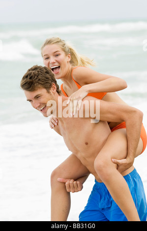 Man giving woman piggyback ride on the beach - Stock Photo