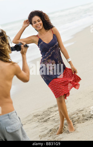Man making a video of a woman on the beach - Stock Photo