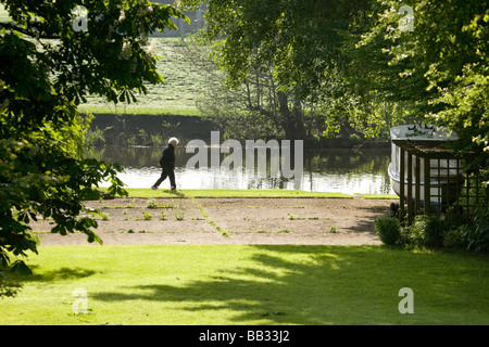 A woman taking an early morning walk along the Thames Path, Wallingford, Oxfordshire, England - Stock Photo
