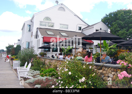 North America, USA, Connecticut, Mystic.  People dining outside under umbrellas at a restaurant on the dock in downtown - Stock Photo