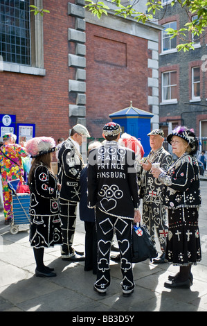 Pearly Kings and Queens talking in the grounds of St Pauls Church in Covent Garden in London.  Photo by Gordon Scammell - Stock Photo