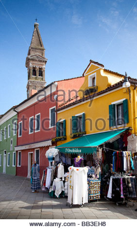 Brightly painted houses on Burano, a lace shop and the leaning Campanile of San Martino church - Stock Photo