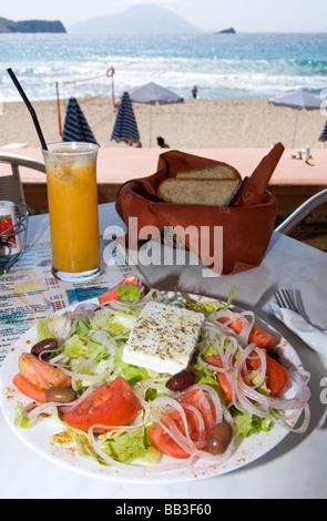 Greek Island Karpathos: Greek salad at the beach. - Stock Photo