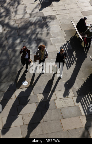 Graphic view of three girls walking on the South Bank with strong shadows London UK - Stock Photo