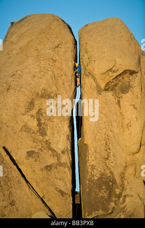 Climber squeezes his way up the gap in a split pillar in Joshua Tree National Park California on a sunny afternoon - Stock Photo