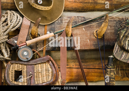 USA, Montana. Fishing ger and hat hang on horn pegs outside of log cabin. - Stock Photo