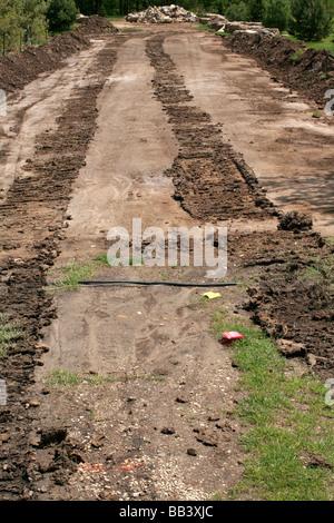 Crawler tractor tracks in mud - Stock Photo