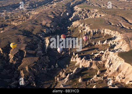 Aerial view of hot air balloons over rough terrain in Cappadocia Turkey - Stock Photo