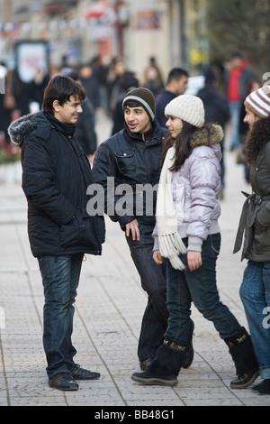 Boys and girls flirt on busy shopping street in Baku Azerbaijan. - Stock Photo