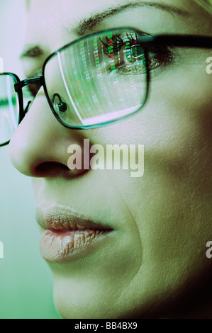 Females Face with Spectacles Reflecting a Computer Screen Display of Stock Market Prices - Stock Photo