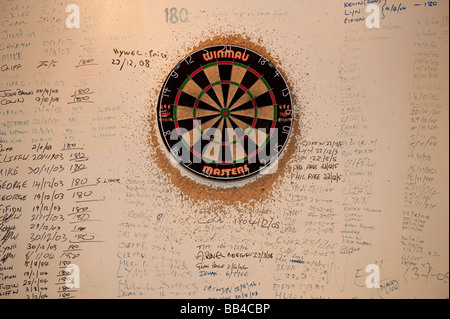 Dartboard in a pub with the names of men who have scored treble top maximum points 180 written on the wall all around - Stock Photo