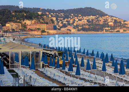 Beach along Promenade Des Anglais street in Nice, France on the French Riviera, as the full moon is rising and the - Stock Photo