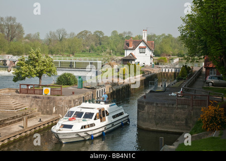 Cruiser exiting the lock on the River Thames at Goring Oxfordshire Uk - Stock Photo
