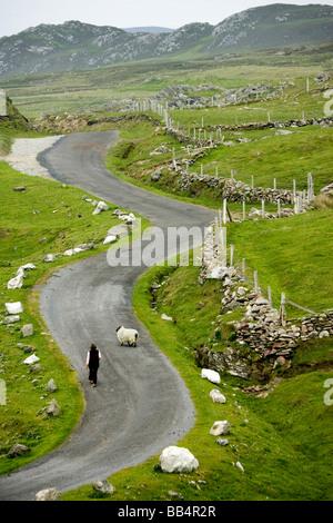 Ireland, County Mayo, Achill Island, Minaun Cliffs. Woman walks on a winding road in the Irish countryside. - Stock Photo