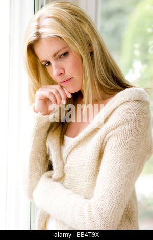 Woman looking sad out of window - Stock Photo
