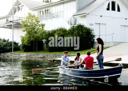 two couples in a rowboat in front of a house - Stock Photo