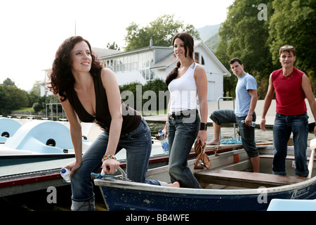 two couples are getting out from a rowboat - Stock Photo