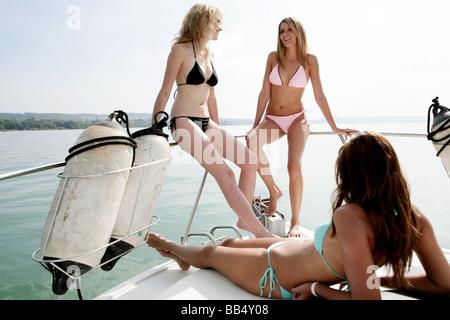 three young women in bikini on a yacht - Stock Photo