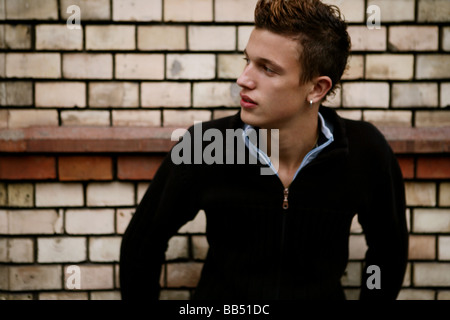 teenager male in front of a brick wall - Stock Photo