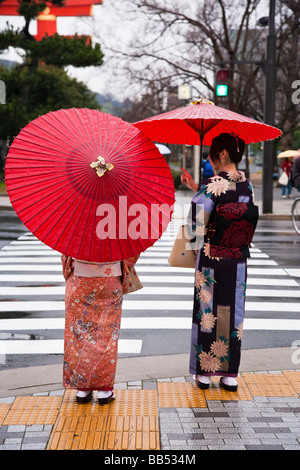 Asia Japan Honshu Kansai Region Kyoto two ladies in traditional Japanese Kimono crossing the street - Stock Photo