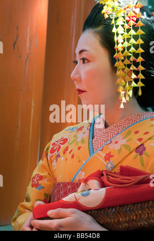 Geisha holding an ornate red umbrella, Fushimi Inari Taish, Kyoto, Kansai Region, Honshu, Japan, Asia - Stock Photo