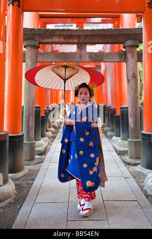 Geisha holding an ornate red umbrella, Fushimi Inari Taish, Kyoto, Kansai Region, Honshu, Japan, Asia - Stock Photo