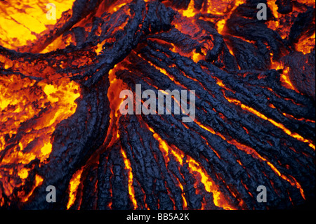 Molten Pahoehoe lava flowing at night from the erupting Kilauea Volcano, in Volcanoes National Park, Hawaii, USA - Stock Photo